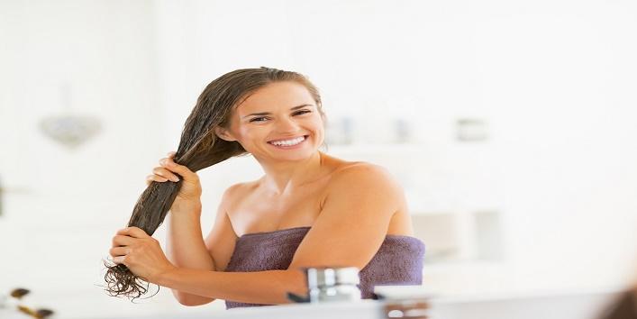 Happy young woman applying hair mask in bathroom