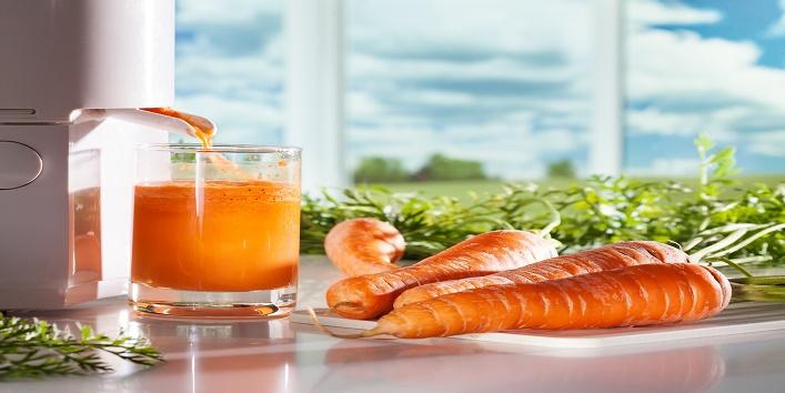 Fresh carrot juicFresh carrot juice and juicer on window backgrounde