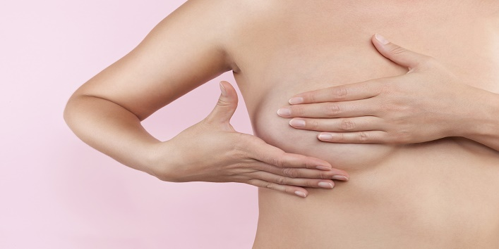 Beautiful girl gently touching her breast. Breast cancer concept. Breast self examination.